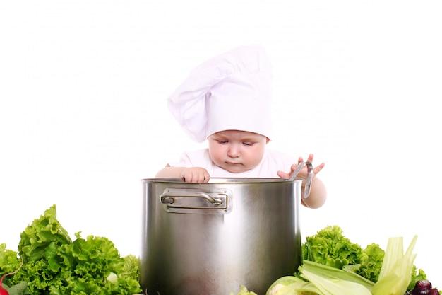 Baby met hoed's chef-kok omringd door groenten