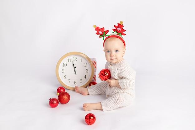 Baby met klok, cadeau en kerstballen op een witte geïsoleerde achtergrond, ruimte voor tekst, nieuwjaar en kerstconcept