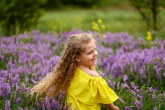 Baby met krullen die op een gebied van lavendel spinnen, gekleed in een gele zomerjurk, zomeravond