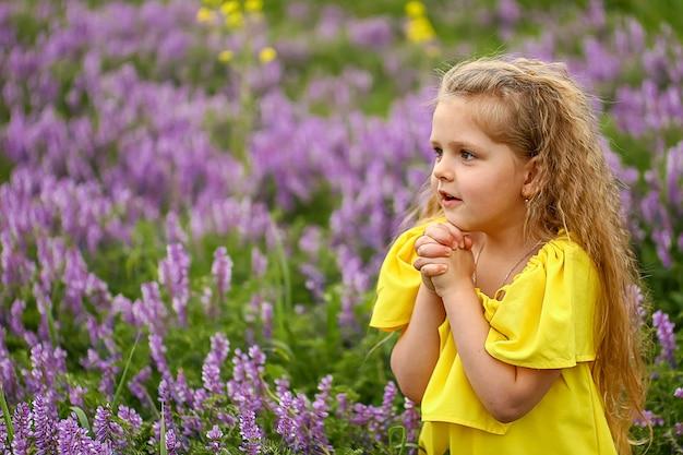 Baby met krullen in een veld van lavendel, gekleed in een gele zomerjurk, zomeravond