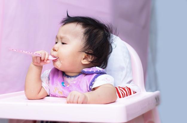 Baby met lepel zitten in een eetkamerstoel