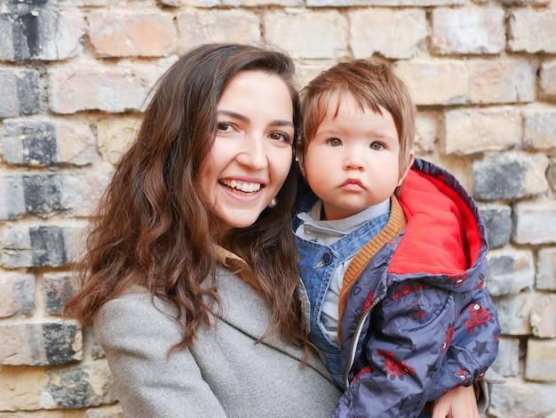 Baby met moeder op een bakstenen muur in warme kleren. gelukkige en jonge moeder die en haar baby zitten houden. liefde en familie concept.