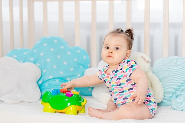 Baby met speelgoed in de voederbak thuis