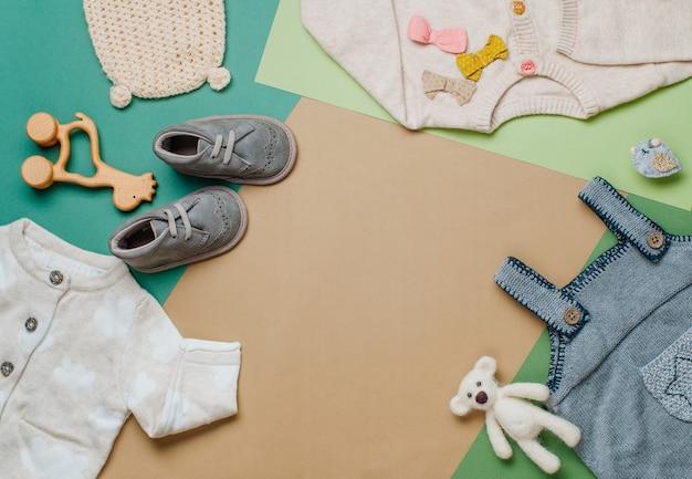 Baby natuurlijk materiaal kleding concept. babykleding en schoenen op neutrale achtergrond met lege ruimte voor tekst. bovenaanzicht, plat gelegd.