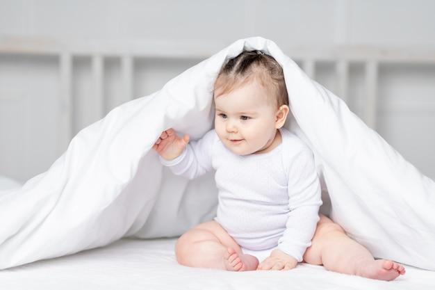 Baby onder de deken op het bed thuis, het concept van familie en kinderen