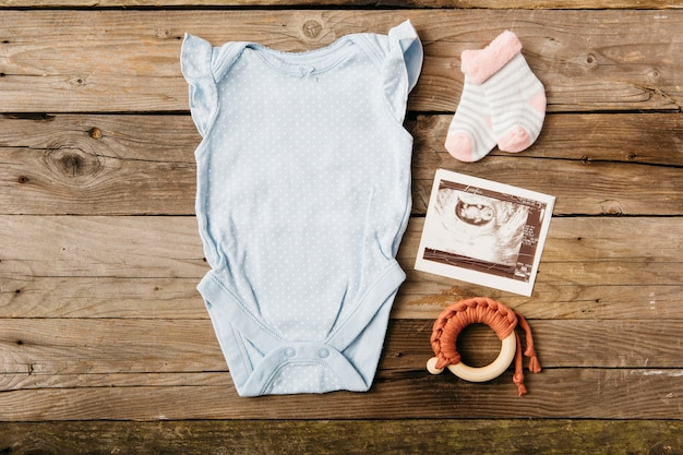 Baby onesie met paar sokken; echografie foto en speelgoed op houten tafel
