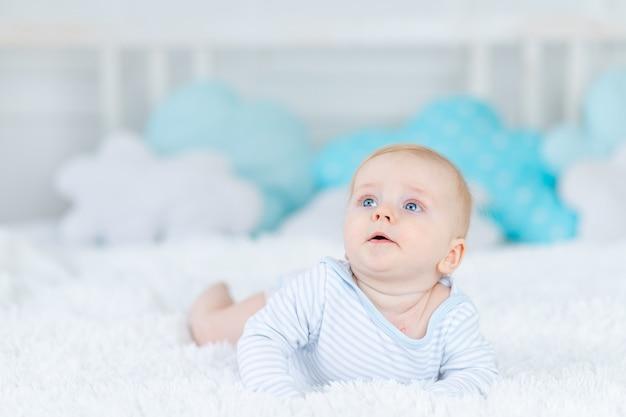 Baby op bed in blauwe pyjama gaat naar bed of wordt 's ochtends wakker, babyjongen blond zes maanden