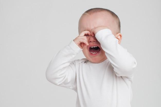 Baby op een witte achtergrond in een witte pyjama