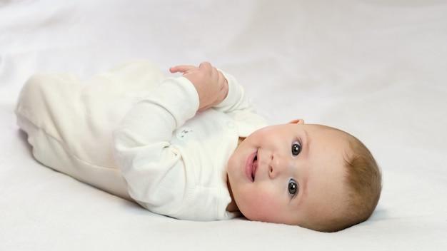 Baby op een witte achtergrond ligt lachend. selectieve aandacht kind.