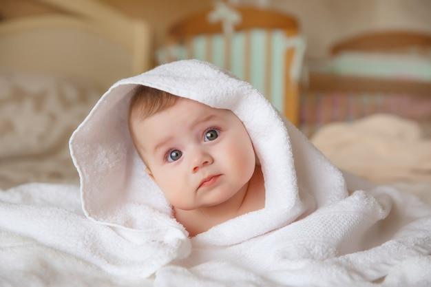 Baby, op het bed in de slaapkamer, handdoek, omslagdoek, glimlach