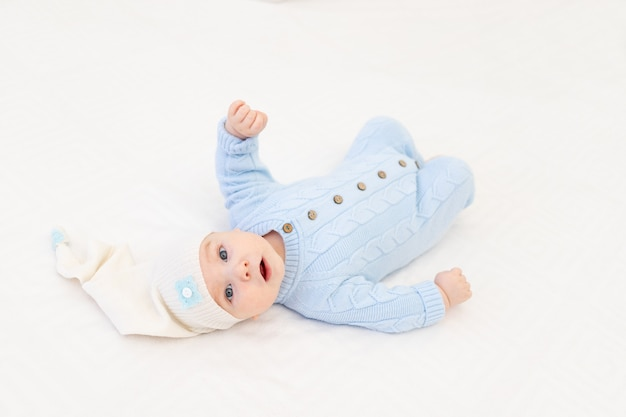 Baby op het bed in een slaapmuts. textiel en beddengoed voor kinderen. baby's ochtend
