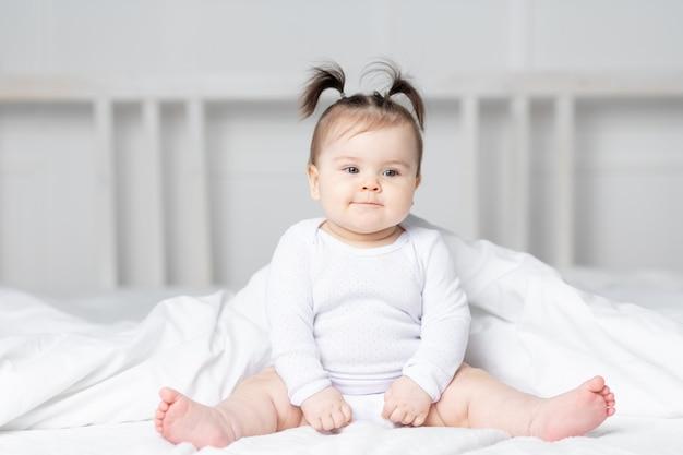 Baby op het bed thuis, het concept van een gelukkig liefdevol gezin en kinderen