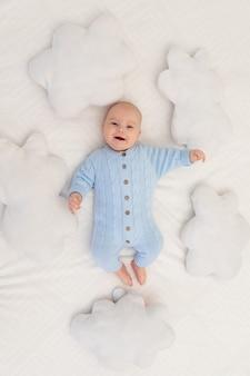 Baby op het bed tussen de wolkenkussens. textiel en beddengoed voor kinderen.