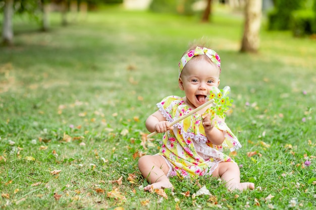Baby op het gazon loopt in de zomer in gele kleren, ruimte voor tekst