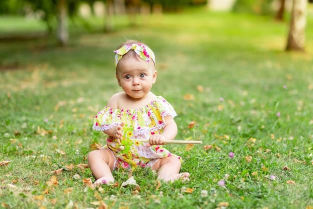Baby op het gazon loopt in de zomer in gele kleren