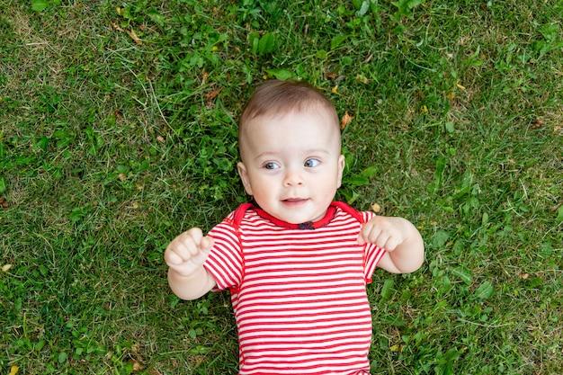 Baby op het gras of het groene gazon baby wandelen buiten in de zomer plaats voor tekst