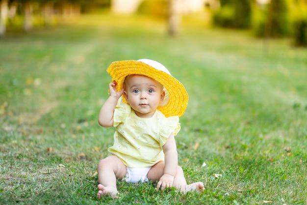 Baby op het gras of het groene gazon met een hoed in de zomer