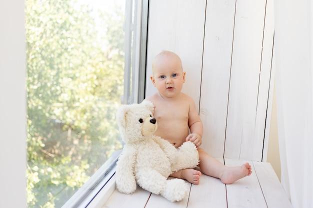 Baby op het raam met een teddybeer in luiers thuis
