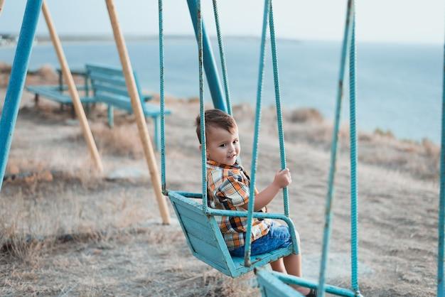 Baby op schommel, slingert in de buurt van de zee, in shirt en spijkerbroek