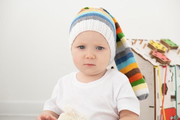 Baby peuter jongen in grappige hoed en wit t-shirt spelen met drukke bord en teddybeer thuis.