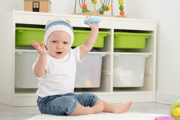 Baby peuter jongen in grappige hoed spelen met piramide thuis. games ontwikkelen voor kinderen.