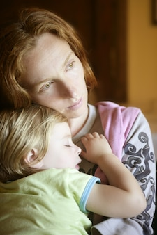Baby peuter meisje slaapt in moeder armen