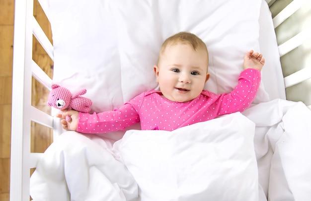 Baby peuter speelt in de wieg. selectieve aandacht.