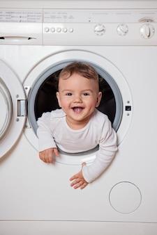Baby piept uit de wasmachine. de jongen speelt verstoppertje. geluk en vreugde.