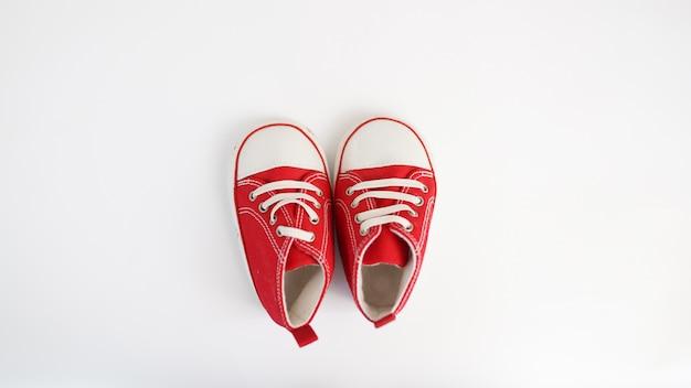 Baby rode tennisschoenen die op witte achtergrond worden geïsoleerd.