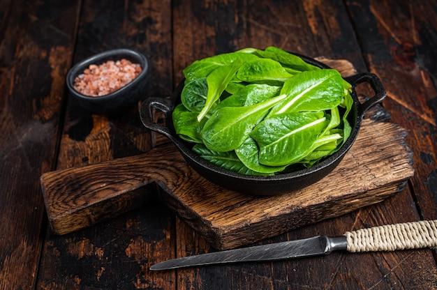 Baby romain groene salade bladeren in pan. donkere houten achtergrond. bovenaanzicht.