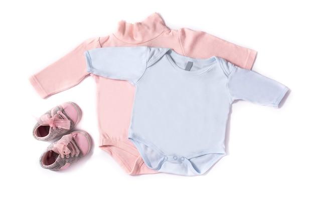 Baby rompertjes en schoenen geïsoleerd op een witte achtergrond
