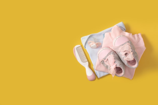 Baby rompertjes, schoenen, fopspeen en haarkam op gele ondergrond