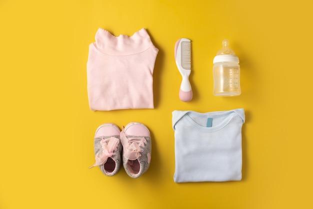 Baby rompertjes, schoenen, zuigfles, fopspeen en haarkam op geel oppervlak.