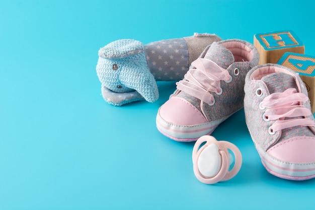 Baby rompertjes, schoenen, zuigfles, fopspeen en speelgoed op blauwe ondergrond