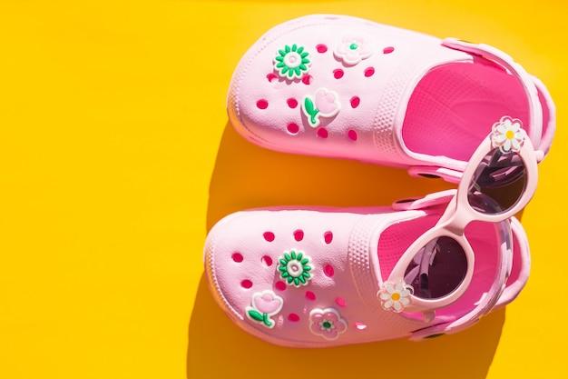 Baby roze pantoffels met zonnebril op gele achtergrond.