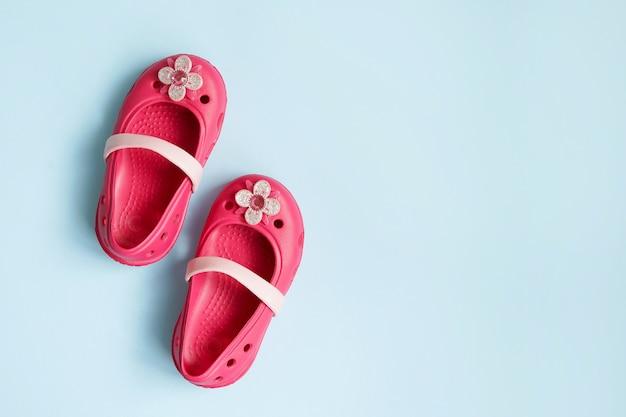 Baby roze rubberen zomer schoenen op blauwe muur met kopie ruimte