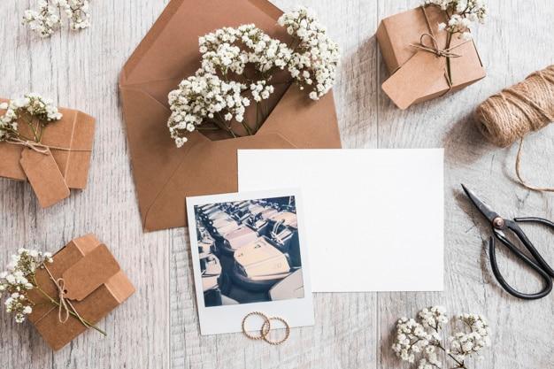 Baby's-adem bloemen in de envelop met blanco papier; trouwringen; spoel en polaroidframe