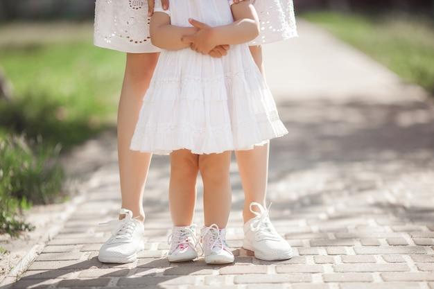 Baby's eerste stappen. klein kind probeert te lopen. moeder en haar kleine schattige dochter houden door de handen. onherkenbare moeder en haar dochter dragen sneakers of keds