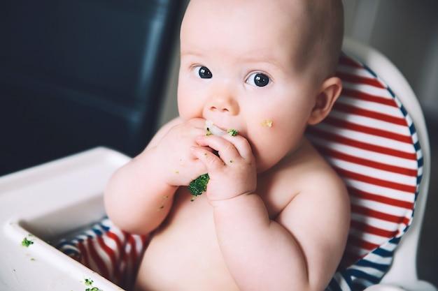 Baby's eerste vaste voedsel rommelige lachende baby eet met vingers groenten broccoli in kinderstoel