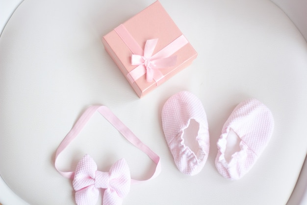 Baby's laarsjes met roze strik en geschenkdoos op lichte ondergrond