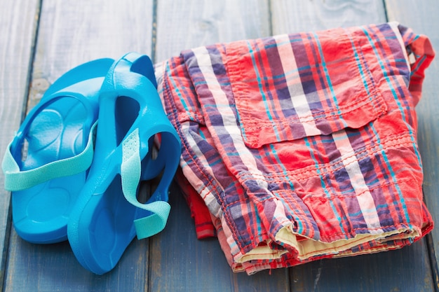 Baby's slippers en shorts op blauwe houten tafel