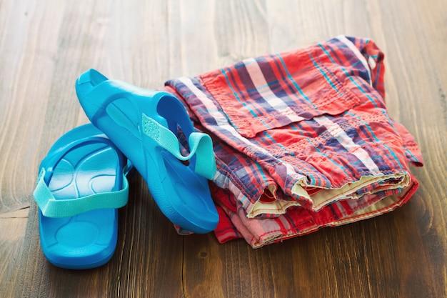 Baby's slippers en shorts op bruine houten tafel