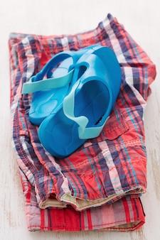 Baby's slippers en shorts op witte houten tafel