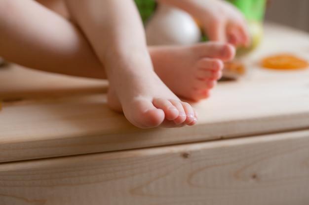 Baby's voeten op een houten tafel met fruit close-up