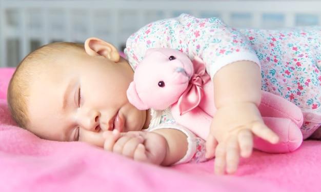 Baby slaapt met een beer. selectieve aandacht. mensen. Premium Foto