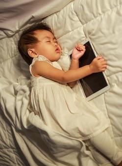 Baby slaapt op bed na het spelen van tablet