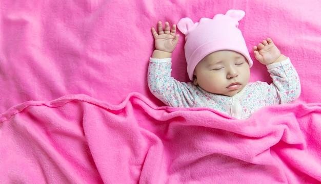 Baby slaapt op een roze bed. selectieve aandacht. mensen.