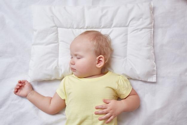 Baby slaapt op een wit kussen.