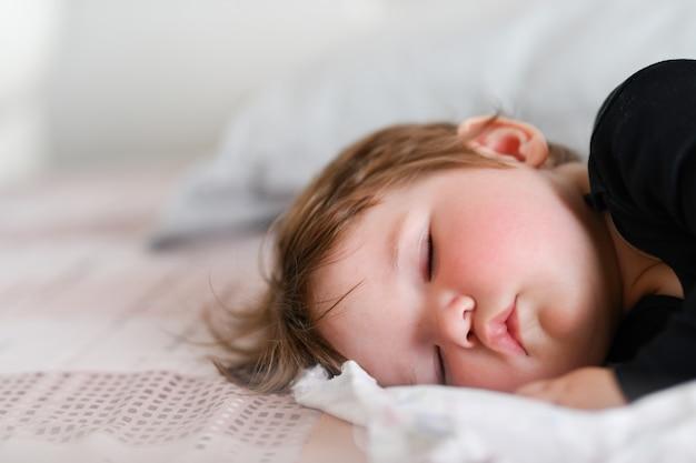 Baby slaapt overdag. gezonde slaap overdag voor de pasgeborene. het kind slaapt in een orthopedische kindercocon op het bed. kinderrust na actief spelen met ouders