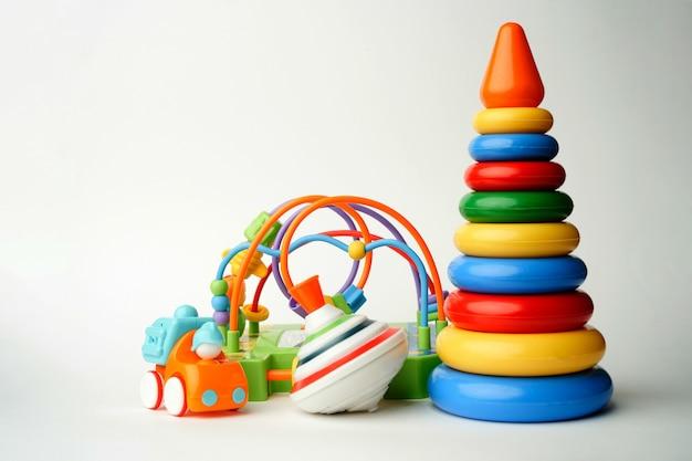 Baby speelgoed collectie op wit oppervlak met kopie ruimte. plastic piramidespeelgoed met zweefmolen en auto.